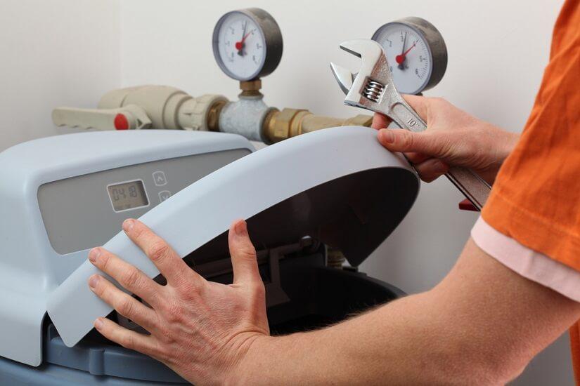 Hombre instalando un descalcificador volumétrico con pantalla