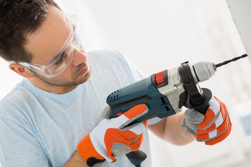 Hombre perforando una pared con un taladro atornillador
